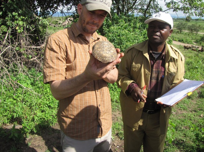 Tuma and Mwaya inspect a pancake tortoise near Kwa Kuchinja, Tanzania